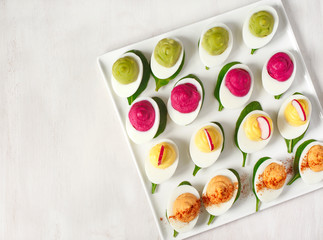 A plate of deviled eggs on grey background, top view