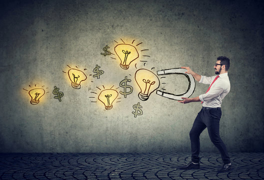 Business man attracts bright ideas light bulbs with a magnet
