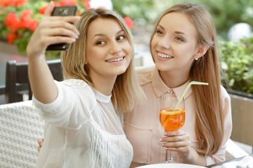 Selfies! Two beautiful girls taking selfie after lunch