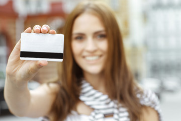 Obraz The thing you need for shopping. Selective focus shot of a young smiling brunette shopper showing credit card - fototapety do salonu