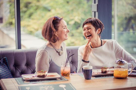 Laughing aged women enjoying meeting in cafe