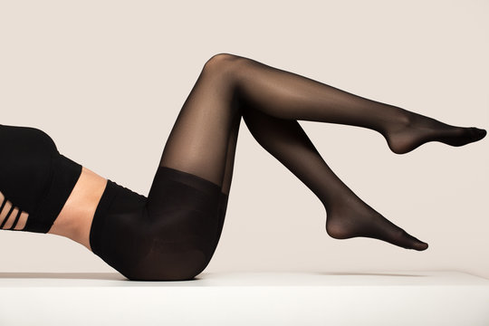 legs in black nylon pantyhose. Expensive stylish tights