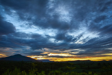 Landscape dramatic cloud sunset of yellow and blue dark sky on nature mountain