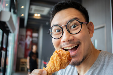Funny face of man eat fried chicken in the franchise cafe.