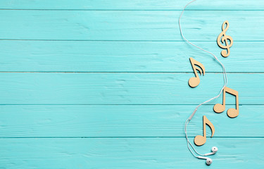 Flat lay composition with music notes, earphones and space for text on color wooden background