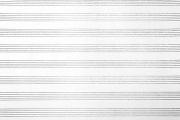 Paper with empty staves for music notes as background, top view