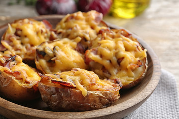 Bowl of baked potatoes with cheese and bacon on table, closeup