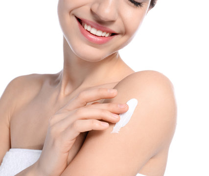 Young woman applying cream on white background, closeup. Beauty and body care