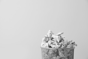 Metal bin with crumpled paper against light background, space for text