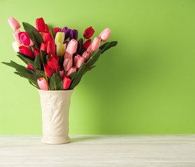 Colorful tulips in vase on white table wall green background