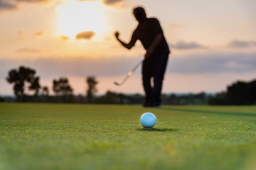 Silhouette golfer showing happiness when win in game , white golf ball on green grass of golf course with blur background.