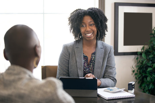 Black female businesswoman in an office with a client giving legal advice about taxes or financial loans. The woman could be a lawyer or a cpa accountant.