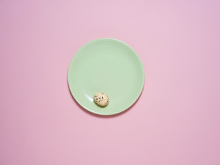 A green plate on a pink background with an Easter decoration.