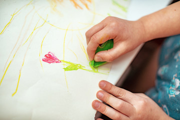 the child draws a flower on paper with wax crayons made with his own hands