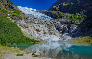Norwegian landscape with milky blue glacier lake, glacier and green mountains. Norway