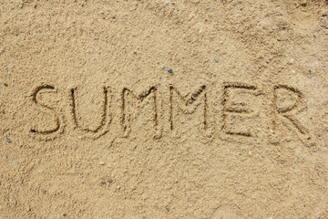 Summer word written on the sand at the beach, natural background