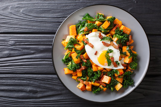 Delicious breakfast of sweet potato with kale, bacon and fried egg close-up on a plate. horizontal top view