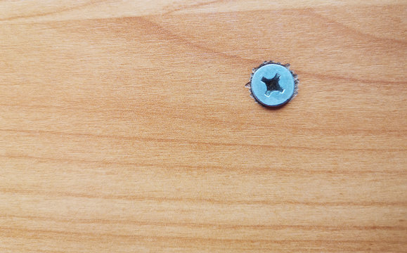 Top view of brown table with flat wood screws and empty space for text.