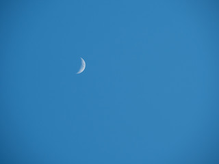 Crescent moon on blue sky background.