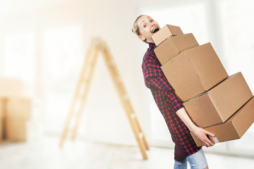 woman moving into new apartment holding stack of cardboard boxes