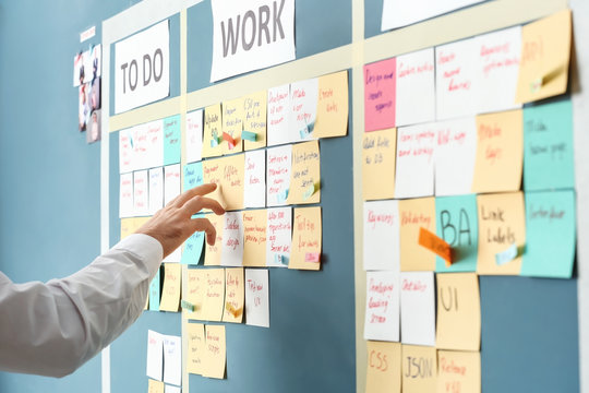 Young man near scrum task board in office
