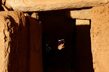 A security guard takes photographs at the megalithic Mnajdra Temples during the vernal equinox marking the beginning of Spring, outside Qrendi