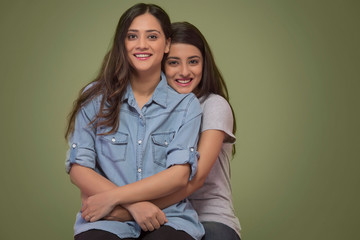 Studio shot of two smiling young teenager girls sitting in a room holding each other