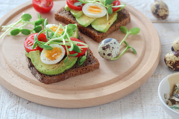 Healthy sandwiches with avocado, tomato, quail eggs and sunflowers micro greens (sprouts) on a white wooden background