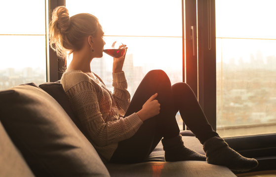 Woman sitting on the sofa, drinking red wine while looking out from the window