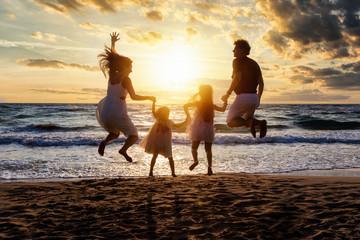 Glückliche Familie im Urlaub springt vor Freude am Strand während des Sonnenunterganges in die Luft