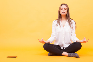 Millennial girl taking a break from her phone and practicing meditation over yellow background