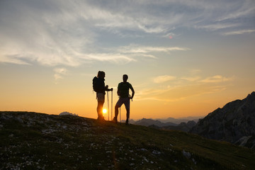 SILHOUETTE Young male and female hikers rest and observe the sunset after ascent