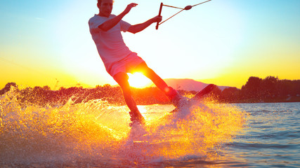 LENS FLARE, CLOSE UP: Young surfer wakeboarding and jumping 180 ollie at sunset Wall mural