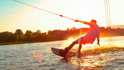 SUN FLARE: Unrecognizable athletic man wakesurfing on the lake at golden sunset. Wall mural