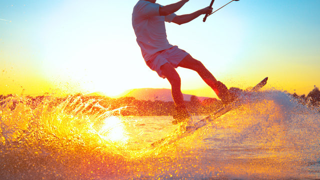 SUN FLARE: Cool surfer dude does 180 ollie while wakeboarding on sunny evening