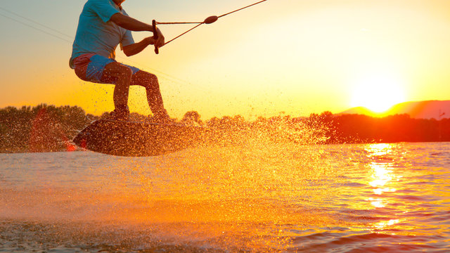 CLOSE UP: Cool wakeboarder does a 180 ollie while speeding across the lake.