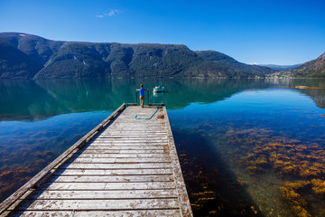 Beautiful Nature Norway natural landscape with pier for boats, fjord and mountain.