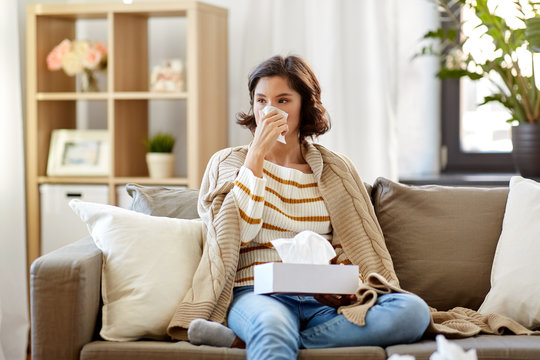 healthcare, cold, hygiene and people concept - sick woman blowing her runny nose in paper tissue at home