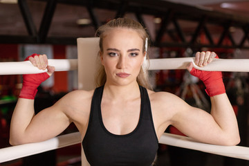 young strong muscular girl standing in the corner of the Boxing ring in red Boxing bandages and waiting for the start of training or combat posing for the camera and grinning