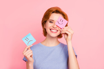 Obraz Close-up portrait of her she nice cute charming attractive cheerful girl wearing casual blue t-shirt holding in hands two draw notes positive good choice isolated on pink pastel background - fototapety do salonu