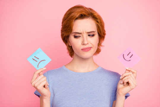 Close-up portrait of her she nice cute charming attractive puzzled girl wearing casual blue t-shirt holding in hands two draw notes sad and joy isolated on pink pastel background