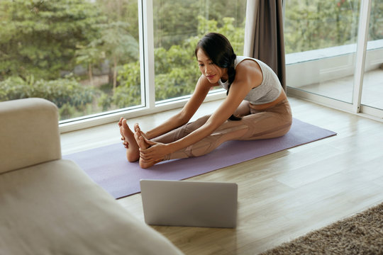 Yoga fitness. Girl stretching body at home using computer