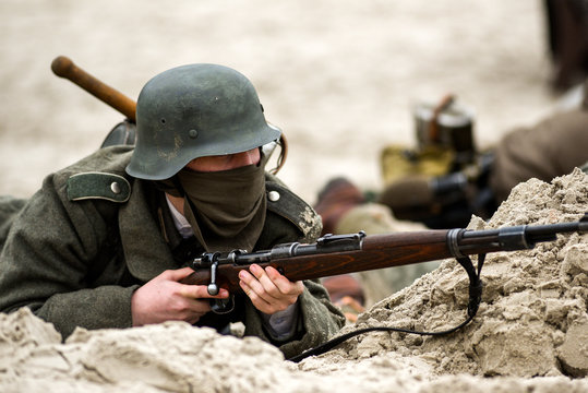 A German soldier in a trench with a rifle in his hand. Historical reenactment of the battle.