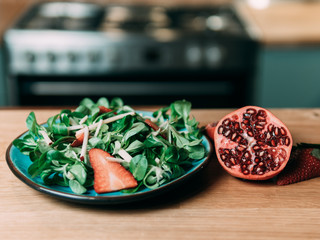 Salad and pomegranate on kitchen table