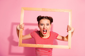 Portrait of her she nice cute charming attractive glamorous aggressive girl in striped t-shirt holding in hands wooden frame trying to break rules borders life lifestyle isolated over pink background
