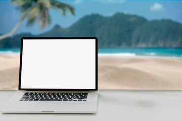 Laptop with blank screen on table and sea background