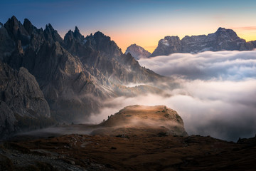 dramatic view of dolomites mountains above the clouds in the tre cime di lavaredo national park. foggy mountain landscape during sunset, South Tyrol. Fototapete