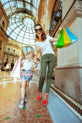 mother and daughter travellers with colorful shopping bags