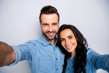 Close up photo of cute sweethearts married  spouses making photos memories wearing blue denim clothes isolated over grey background