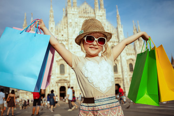 modern tourist girl with colorful shopping bags rejoicing